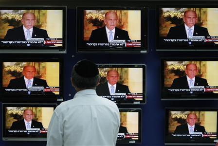 A man watches televisions broadcasting a statement delivered by Israel's Prime Minister Ehud Olmert at a shopping mall in Jerusalem July 30, 2008. REUTERS/Baz Ratner