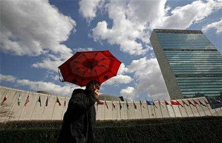 A man passes with an umbrella in front of the United Nations Headquarters in New York, March 24, 2008. REUTERS/Mike Segar