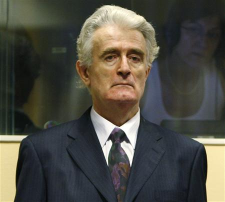 Former Bosnian Serb leader Radovan Karadzic stands in the court room of the International Criminal Tribunal for the Former Yugoslavia at the start of his initial appearance in The Hague July 31, 2008. Karadzic faces a U.N. war crimes judge for the first time to answer charges of genocide for his actions in the 1992-95 Bosnia war. REUTERS/Jerry Lampen