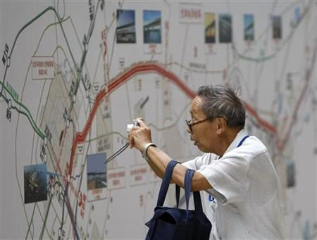 A man takes pictures of the route map for the new Beijing-Tianjin Intercity Railway, August 1, 2008. The express link railway opened on Friday, in time for the upcoming Beijing Olympics. REUTERS/Kim Kyung-Hoon