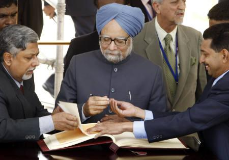 Prime Minister Manmohan Singh prepares to sign a visitor's book at International Airport in Colombo August 1, 2008. REUTERS/Buddhika Weerasinghe