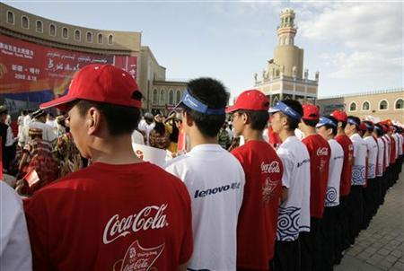 In this file photo men wear t-shirts with the logos of Olympic sponsors Coca Cola and Lenovo during the Olympic torch relay in Kashgar, Xinjiang province June 18, 2008. Olympic sponsors are launching possibly the largest advertising and marketing campaign ever, aiming to etch their brands in the minds of a new generation of Chinese consumers for far beyond the upcoming Games. REUTERS/Reinhard Krause