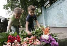 <p>Due bambini depongono fiori davanti alla porta della casa di Alexander Solzhenitsyn. REUTERS/Alexander Natruskin (RUSSIA)</p>