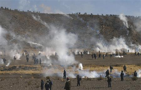 Bolivian riot police (on top of ridge) fire tear gas canisters at workers of the Huanuni mine in Caihuasi near Oruro August 5, 2008. REUTERS/La Patria newspaper