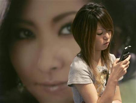 A Japanese girl checks her mobile phone in Tokyo's Shibuya district June 19, 2007. REUTERS/Yuriko Nakao