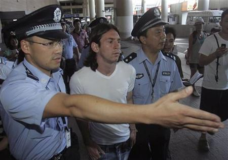 Argentina's soccer player Lionel Messi (C) arrives at the Shanghai Pudong International Airport in Shanghai August 1, 2008. Messi is set to miss the Olympic Games soccer tournament after the Court of Arbitration for Sport (CAS) said Barcelona was not obliged to release him. REUTERS/Stringer