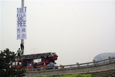 A protester descends a pole to an awaiting policeman after hanging a banner which reads 'Tibet will be free' near the National Stadium, also known as the Bird's Nest, before the Beijing Olympic Games in this photo released by Students for a Free Tibet, August 6, 2008. REUTERS/Students for a Free Tibet/Handout