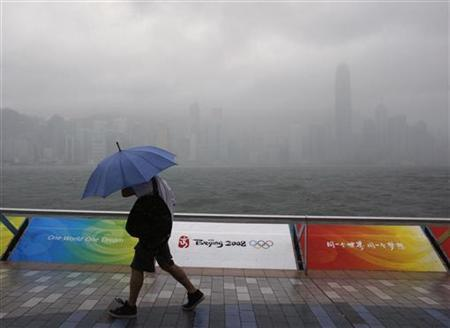 A man braves strong winds and heavy rains under a tropical typhoon attack in front of Olympics decoration on the Hong Kong waterfront August 6, 2008. Tropical downpours are becoming more frequent and the trend seems worse than expected, bringing greater risks of flash floods, scientists said on Thursday. REUTERS/Bobby Yip