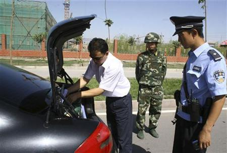 A policeman checks a vehicle on a highway in Hami, Xinjiang Uigur Autonomous Region August 7, 2008. REUTERS/Stringer