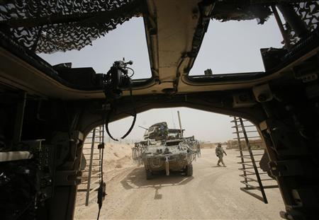 A U.S. soldier from the Second Stryker Cavalry Regiment walks next to a military vehicle near Baquba during security operations in Diyala province August 5, 2008. REUTERS/Andrea Comas