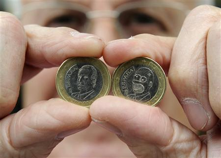 Candy shop owner Jose Martinez shows an official Spanish 1 Euro coin with the face of Spanish King Juan Carlos (L) and another one altered to look like a face of cartoon character Homer Simpson in the northern Spanish town of Avile August 8, 2008. Martinez found the Homer Simpson coin in his shop's cash register while counting the days' transactions last week. REUTERS/Eloy Alonso