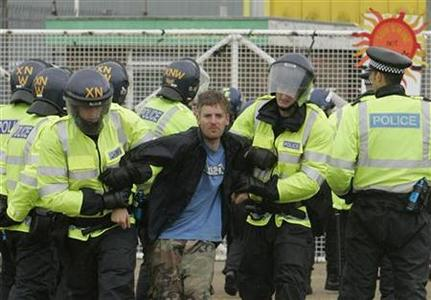 A protester is removed by police from in front of the gates of the Kingsnorth Power Station near Rochester in Kent, August 9, 2008. REUTERS/Luke MacGregor