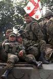 <p>Грузинские солдаты сидят на танке, покидающем окрестности столицы Южной Осетии Цхинвали, 10 августа 2008 года. Генштаб российской армии подтвердил в воскресенье, что Грузия начала вывод своих войск из Южной Осетии. (REUTERS/Gleb Garanich)</p>
