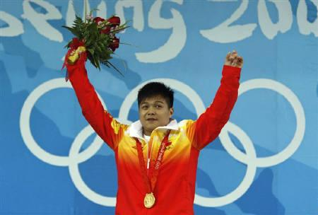 Long Qingquan of China poses with his gold medal in the men's 56kg weightlifting competition at the Beijing 2008 Olympic Games August 10, 2008. REUTERS/Oleg Popov