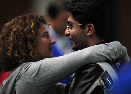 Abhinav Bindra (R) is hugged by his coach Gabriele Buhlmann after the men's 10m air rifle final at the Beijing 2008 Olympic Games August 11, 2008. Bindra will get a free lifetime railway pass for winning his nation's first solo title in an Olympics on Monday. REUTERS/Desmond Boylan