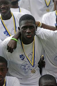 Sierra Leone U15 football team FC Johansen player Issa Koroma, nicknamed 'Madam', wears his Mittnorden Cup silver medal as the team poses in Freetown, August 8, 2008. Striker Koroma scored the most goals of anyone at the Swedish youth cup, in which Sierra Leone was the first African country to compete in the competition's 27-year history. FC Johansen won silver at the tournament in Sweden, but were hailed as champions in their poor West African homeland, because they all came home. Sierra Leone is bottom of the U.N. development rankings and its athletes frequently vanish when travelling abroad for sporting fixtures in order to seek asylum, meaning many Western countries now simply refuse to let them in. Picture taken August 8, 2008. REUTERS/Katrina Manson (SIERRA LEONE)