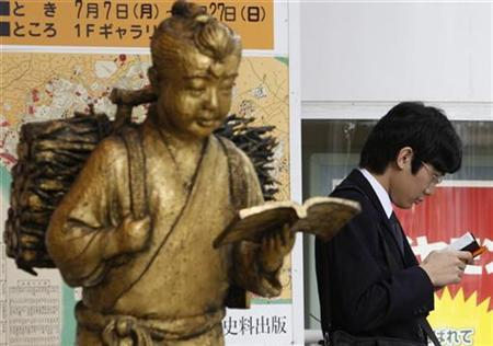 A man reads a book next to a statue in front of a book store in Tokyo July 15, 2008. REUTERS/Kim Kyung-Hoon