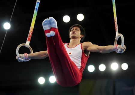 8月12日、北京五輪体操男子団体で日本が銀メダルを獲得。写真はつり輪を行う冨田(2008年 ロイター/Dylan Martinez)