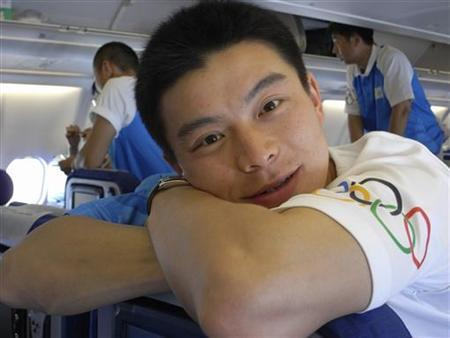A guarder of Beijing Olympic torch relay known as ''Second Brother on the Right'' poses for a photo on an airplane from Sanya to Beijing, May 4, 2008. REUTERS/China Daily