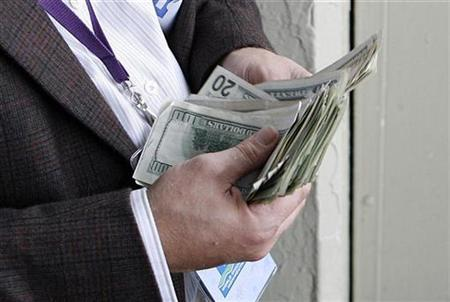 A man holds a wad of money in an undated file photo. REUTERS/File