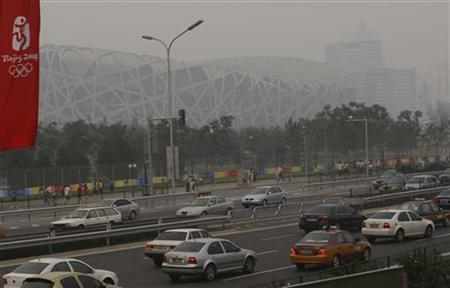 The National Olympic Stadium, also known as the Bird's Nest, is seen as cars drive past on a hazy day in Beijing near the Olympic Green in Beijing August 4, 2008. REUTERS/Gil Cohen Magen