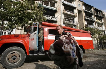 A Georgian man carries his belongings from his damaged home in Gori, some 80 km (50 miles) from Tbilisi August 11, 2008. The simmering conflict between Russia and its small, former Soviet neighbour erupted last Thursday when Georgia sent forces into South Ossetia, a pro-Russian province that threw off Georgian rule in the 1990s. REUTERS/David Mdzinarishvili