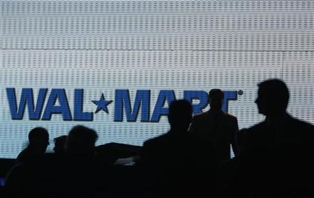 Wal-Mart shareholders are silhouetted against a video screen Wal-Mart Shareholders Meeting in Fayetteville, Arkansas, June 6, 2008. REUTERS/Jessica Rinaldi