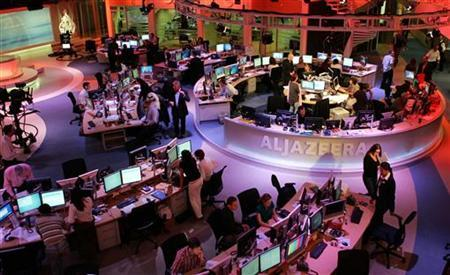 Staff work at the English-language newsroom at the headquarters of the Qatar-based Al Jazeera satellite channel in Doha, November, 14, 2006. REUTERS/Mohammed Dubbous