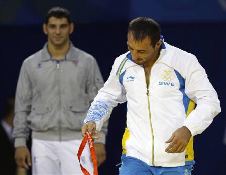 Bronze medallist Ara Abrahamian (R) of Sweden throws his medal on the floor during the medal ceremony for the men's 84kg Greco-Roman wrestling competition at the Beijing 2008 Olympic Games August 14, 2008. REUTERS/Oleg Popov