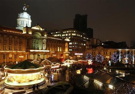 Shoppers browse a German market and carousel in Birmingham, England, December 20, 2007. REUTERS/Darren Staples