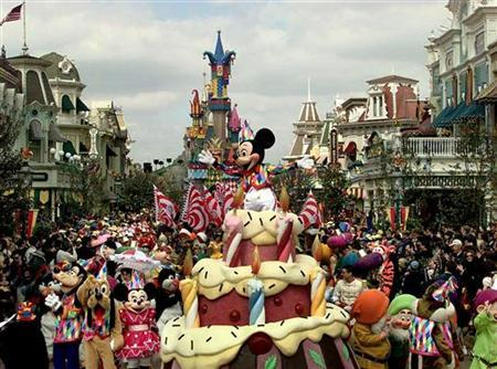 Walt Disney's Mickey Mouse along with various characters waves to the crowd on a giant birthday cake, as Euro Disney's theme park on the edge of Paris, celebrates its fifth anniversary April 12, 1997. REUTERS/Pascal Rossignol