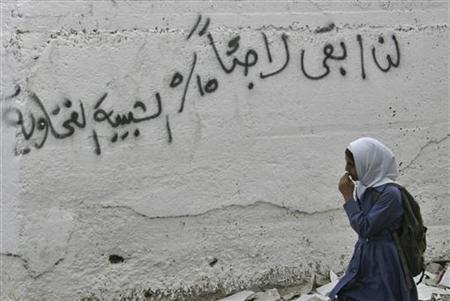 A young Palestinian refugee walks near her school wall at al-Baqaa Refugees camp, outside of Amman, May 15, 2008. The graffiti reads ''I will not stay as a refugee forever''. REUTERS/Muhammad Hamed