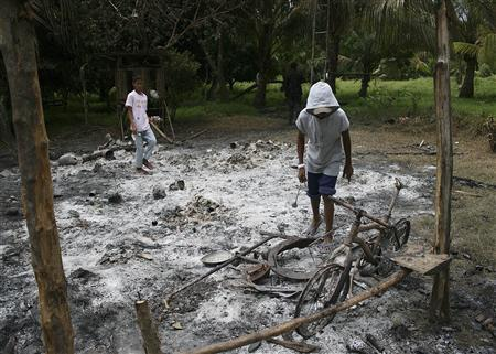 A Filipino boy looks at his bicycle that was burned along with his house by Moro Islamic Liberation Front (MILF) rebels in Takepan village in Pikit, North Cotabato, southern Philippines August 12, 2008. REUTERS/Stringer