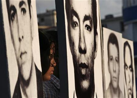Students hold photographs of victims of the 1976 bombing of a Cuban airliner during the resolution of a symbolic trial of anti-Castro Cuban exile Luis Posada Carriles outside the U.S. diplomatic mission in Havana May 15, 2007. REUTERS/Claudia Daut