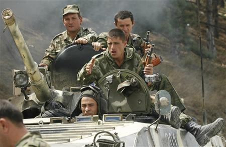Russian servicemen sit on top of an armoured vehicle in the Georgian town of Gori, about 80 km (50 miles) from Tbilisi, August 16, 2008. Russian President Dmitry Medvedev on Saturday signed a ceasefire agreement ending hostilities with Georgia over the breakaway region of South Ossetia, the Kremlin said. REUTERS/David Mdzinarishvili