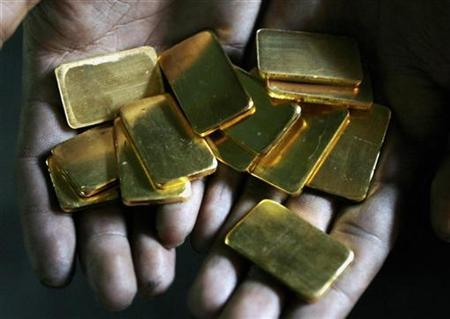 A worker shows gold biscuits at a precious metals refinery in Mumbai March 3, 2008. REUTERS/Arko Datta