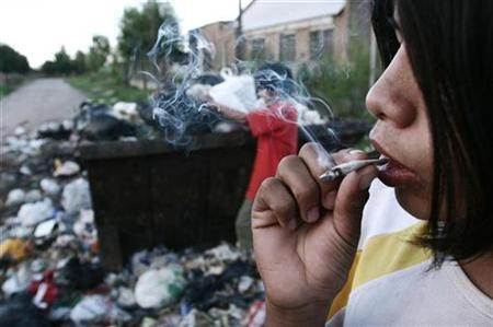 A sixteen-year-old smokes a cigarette laced with ''paco'', a cheap drug made from cocaine paste mixed with other toxic substances in a slum of Rosario, 310 km (193 miles) north of Buenos Aires March 3, 2008. REUTERS/Francisco Guillen