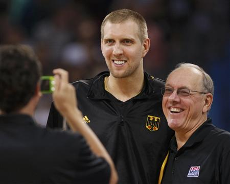 Dirk Nowitzki of Germany (L) and U.S. assistant coach Jim Boeheim (R) have their photo taken after the men's Group B basketball game at the Beijing 2008 Olympic Games August 18, 2008. REUTERS/Lucy Nicholson