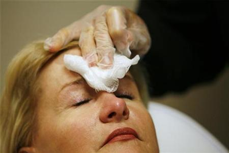 A doctor uses a gauze patch to dab blood from the forehead of a patient after administering an injection of Botox at a walk-in Botox salon in New York July 17, 2007. REUTERS/Lucas Jackson