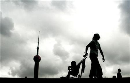 A woman and her child stroll along the Bund in Shanghai August 24, 2004. REUTERS/China Photos
