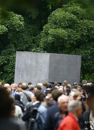People stand in front of the new memorial to homosexuals persecuted by the Nazis, during the inauguration ceremony in Berlin May 27, 2008. The single grey concrete slab is placed in the capital's central Tiergarten park. REUTERS/Johannes Eisele