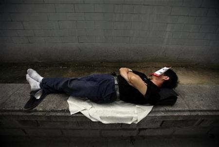 A petitioner sleeps with a bus timetable covering his face on a street outside a government office in Beijing July 20, 2008. REUTERS/David Gray