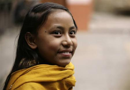Sajani Shakya, 11, a young Nepali girl worshipped by many Buddhists and Hindus as a ''Kumari'', or living goddess, smiles in her home at Bhaktapur in the Nepali capital of Kathmandu March 2, 2008. REUTERS/Shruti Shrestha