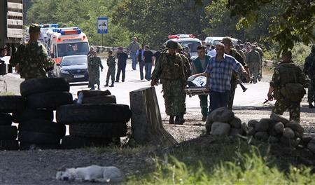 Russian soldiers carry a wounded pilot after Russian and Georgian officials met roadside to hold a prisoner exchange near Kaspi, on the road from Tbilisi to Gori on August 19, 2008. REUTERS/Adrees Latif