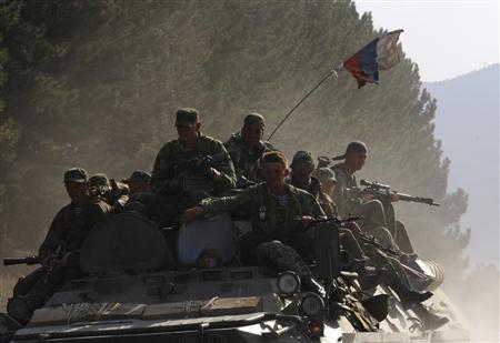Russian soldiers travel on top of an amoured vehicle on a road near the Georgian town of Gori August 18, 2008. REUTERS/Gleb Garanich