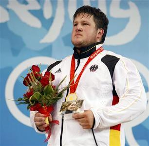 Matthias Steiner of Germany holds a photo of his late wife Susann as he poses with his gold medal in the men's +105kg Group A weightlifting competition at the Beijing 2008 Olympic Games August 19, 2008. REUTERS/Alvin Chan