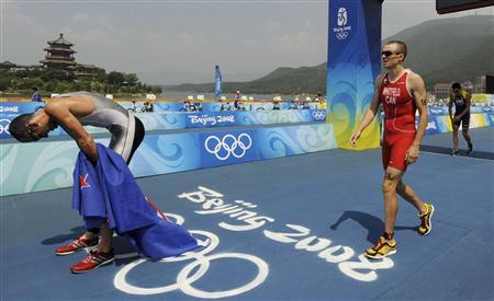 Francisco Javier Gomez (R) of Spain crosses the finish line in fourth place behind Bevan Docherty of New Zealand (L), Simon Whitfield (C) of Canada and Jan Frodeno of Germany (not pictured) during the men's triathlon competition at the Ming Tomb reservoir in the Changping District of northern Beijing at the Beijing 2008 Olympic Games August 19, 2008. REUTERS/Wolfgang Rattay