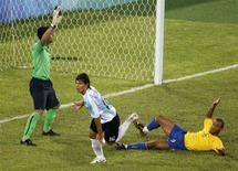 <p>Нападающий сборной Аргентины Серхио Агуэро (в центре) забивает мяч в ворота сборной Бразилии в полуфинале олимпийского турнира в Пекине 19 августа 2008 года. Сборная Аргентины в полуфинале футбольного олимпийского турнира выиграла у национальной команды Бразилии, а команда Нигерии обыграла Бельгию. REUTERS/Shaun Best</p>