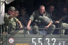 <p>Российские военнослужащие в кузове грузовика, направляющегося к абхазскому городу Гал 11 августа 2008 года. Колонна из двенадцати российских военных грузовиков, двигавшихся со стороны Южной Осетии, пересекла границу России, сообщил корреспондент Рейтер в среду. (REUTERS/Vladimir Popov)</p>