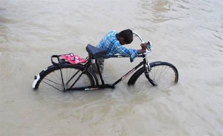 A boy pushes his bicycle on a flooded street in Allahabad August 19, 2008. Floods caused by heavy rains have swamped hundreds of villages in northern India, killing at least 114 people since last week, officials said. REUTERS/Jitendra Prakash